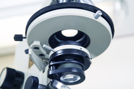 microscope lens: Scientific microscope lens close-up in laboratory white interior. A microscope is an instrument used to see too small objects Stock Photo