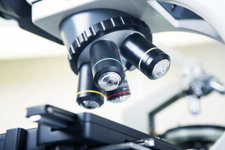 analytical chemistry: Scientific microscope lens close-up in laboratory white interior. A microscope is an instrument used to see too small objects Stock Photo