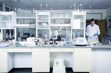 tubo de ensayo: Interior de limpio y moderno blanco médico o químico fondo laboratorio. Concepto de laboratorio con caucásica químico masculina. Plantilla horizontal para un cartel, página web o el prospecto. Foto de archivo