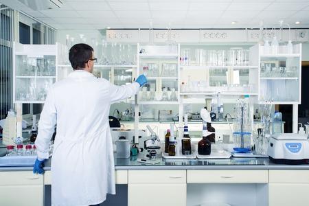 Interieur van schone moderne witte medische of chemisch laboratorium achtergrond. Laboratorium concept met een blanke man chemicus. Horizontale sjabloon voor een poster, webpagina of bijsluiter.
