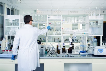 chemical plant: Interior of clean modern white medical or chemical laboratory background. Laboratory concept with caucasian male chemist. Horizontal template for a poster, webpage or leaflet. Stock Photo