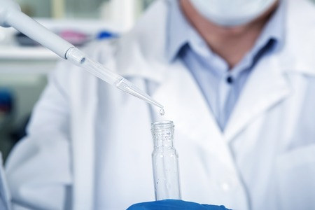 an inoculation: Microbiologist hand cultivating whit inoculation loops in pipette in medical mask, blue rubber gloves and white coat using test tubes at his workplace in the laboratory.