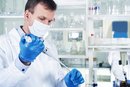 an inoculation: Caucasian male chemist scientific researcher in medical mask, blue rubber gloves and white coat using test tubescultivating whit inoculation loops in pipette at his workplace in the laboratory.