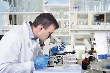 Portrait of caucasian male chemist scientific researcher using microscope in the laboratory interior