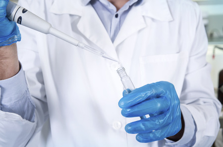 Caucasian male chemist scientific researcher in medical mask, blue rubber gloves and white coat using test tubescultivating whit inoculation loops in pipette at his workplace in the laboratory.