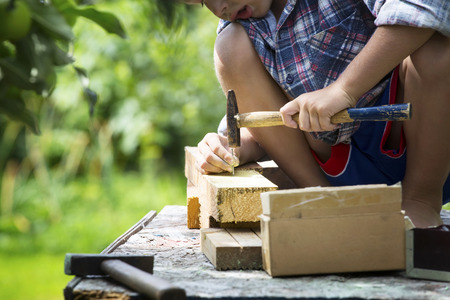 hammer and nails: Boy learns to hammer nails in a garden Stock Photo