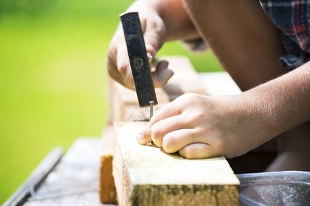 learns: Boy learns to hammer nails in a garden Stock Photo