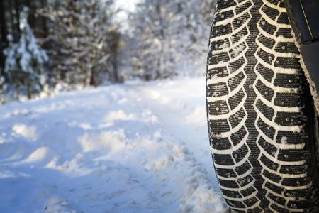 Auto op de winter weg in het hout. Winter banden