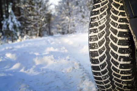 Car on the winter road in the wood. Winter tires