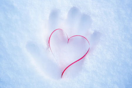 Heart in a snow-covered snowdrift. Concept of Christmas and Valentines Day