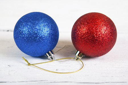 adn: Brilliant  baubles like christmas decoration.  Red adn blue balls isolated on white wooden background. Foto de archivo