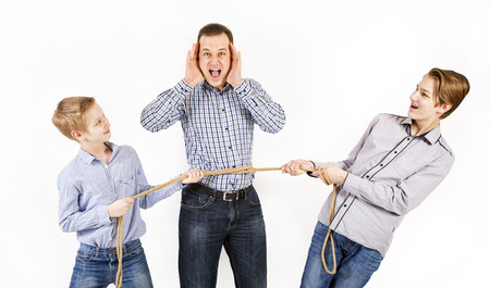 Father and two sons connected by rope Stock Photo