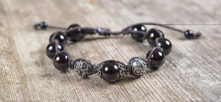Popular Buddhist bracelet shamballa on a wooden background