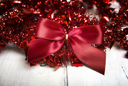 tinsel: Christmas decoration. Red ball and  bow on white wooden background.