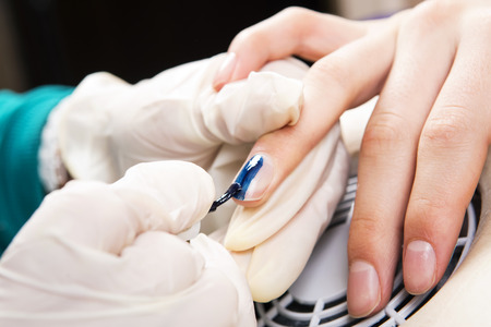 Manicure specialist care by finger nail in beauty salon.