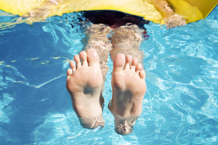 Spa; swimming and rest. Feet in the pool close up