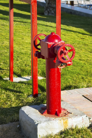 Red fire valve on background of green grass