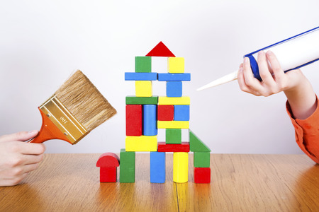 Boys  repair the house from cubes by construction tools.Construction concept Stock Photo