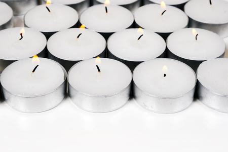glorification: Group of burning round candles on white background