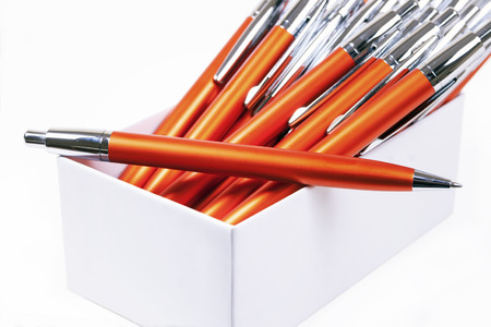 the daily grind:  Orange pens isolated on a white background