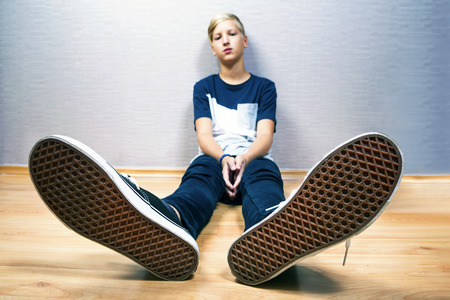 Teenager sits on a floor in the room in jeans and shoes