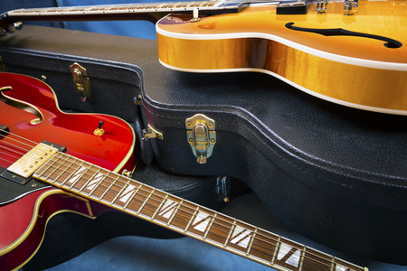 Acoustic guitars in covers in a blue background Standard-Bild