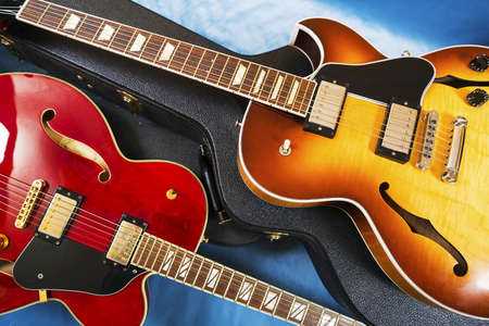 Acoustic guitars in covers in a blue background Stock Photo