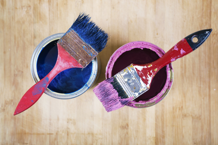 Full of blue and pink paint tines and paint brushes on it, isolated on wooden  background