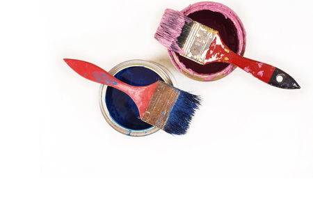 Full of blue and pink paint tines and paint brushes on it, isolated on white  background.  Top view with copy space