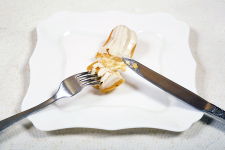 Eating eclair cake, on white plate background.