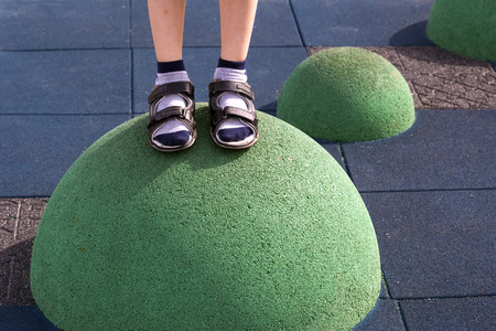 Childrens feet in sneakers and shorts at the playground  balance equipment