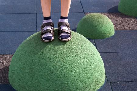 Kindervoeten in sneakers en shorts op de speelplaats balans apparatuur Stockfoto