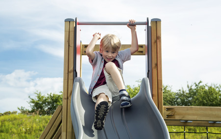 Happy little boy on the playground at the day time
