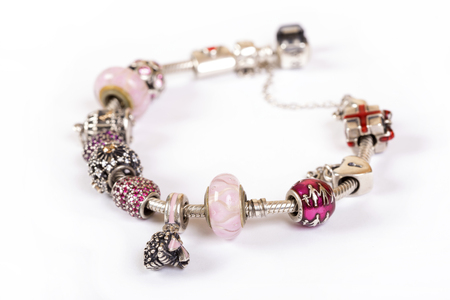 Silver charm bracelet with pink beads isolated on white background Imagens