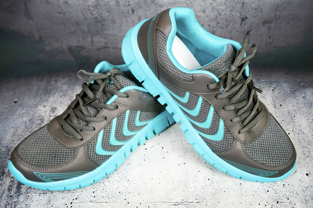 Pair of blue  sports shoes with laces isolated on a concrete background