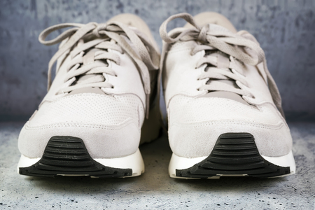 Pair of mens sports shoes on a concrete background