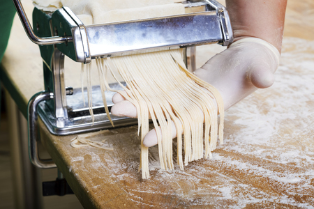 Process of production of  pasta. Fresh pasta and pasta machine on kitchen table Stockfoto