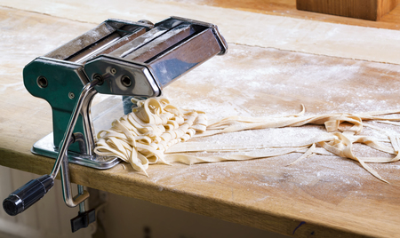 Process of production of  pasta. Fresh pasta and pasta machine on kitchen table Banque d'images