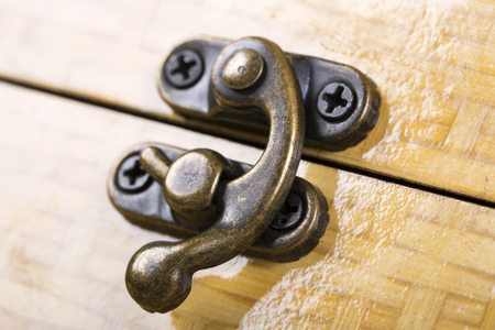 Wooden chest locked to a lock . Macro shot