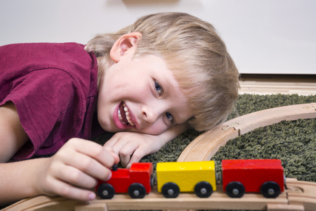 Children play with wooden toy, build toy railroad at home or daycare. Toddler boy play with  train and cars. Educational toys for preschool and kindergarten child.