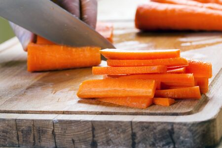 Man cutting carrot on table, closeup. Macro shot Stok Fotoğraf