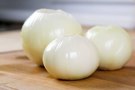 White onion on the wooden board. Preparation for cooking. Healthy eating and lifestyle.