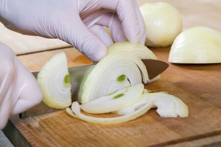 Chefs hands with knife cutting the onion on the wooden board. Preparation for cooking. Healthy eating and lifestyle.