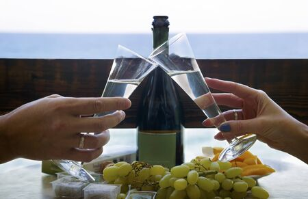 Glasses with champagne in the hands of a wedding couple against the background of pastilles, fruits and sea Stok Fotoğraf