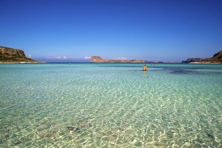 Balos lagoon on Crete island, Greece. Tourists relax in crystal clear water of Balos beach.