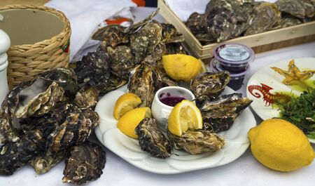 Fresh organic raw oysters with lemons on on traditional and natural wayr of a street market on a fair of traditional products, in Klaipeda, Lithuania Stok Fotoğraf