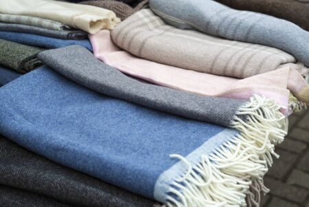 A pile of warm wool scarves on traditional and natural wayr of a street market on a fair of traditional products, in Klaipeda, Lithuania Stok Fotoğraf