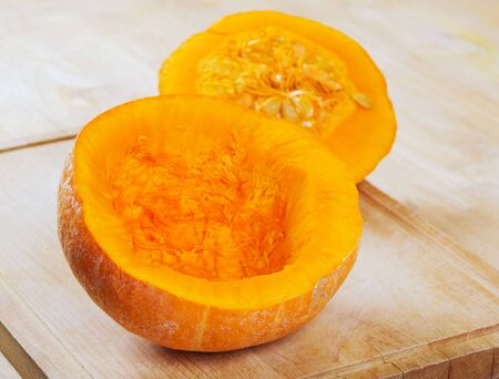 Cut pumpkin on rustic wooden table exposing seeds