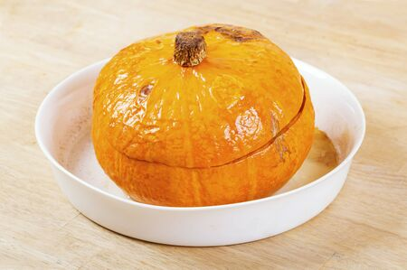 Baked stuffed pumpkin in the kitchen Standard-Bild