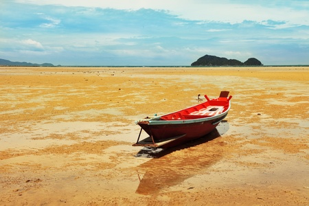 Seascape in Thailand with fisherman boat during low tide. photo